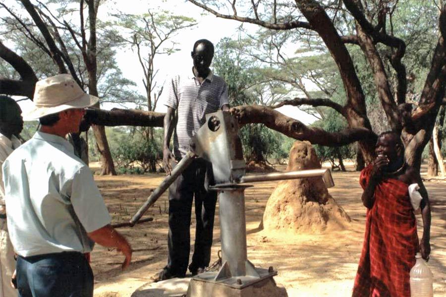 Steve Burgess chats to community members at a new water pump in arid scrub forest in Turkana, Kenya